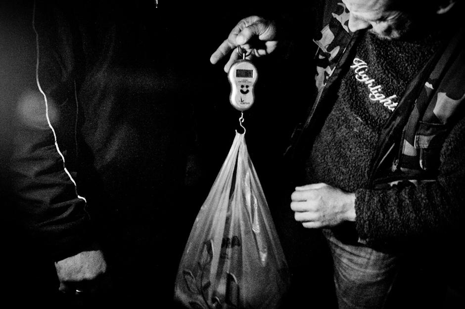 Brakonierius sveria žuvį būsimam pirkėjui. © Karolis Kavolėlis