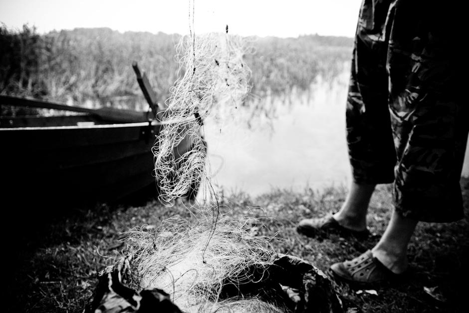 Brakonierius paruošia tinklus žvejybai. © Karolis Kavolėlis