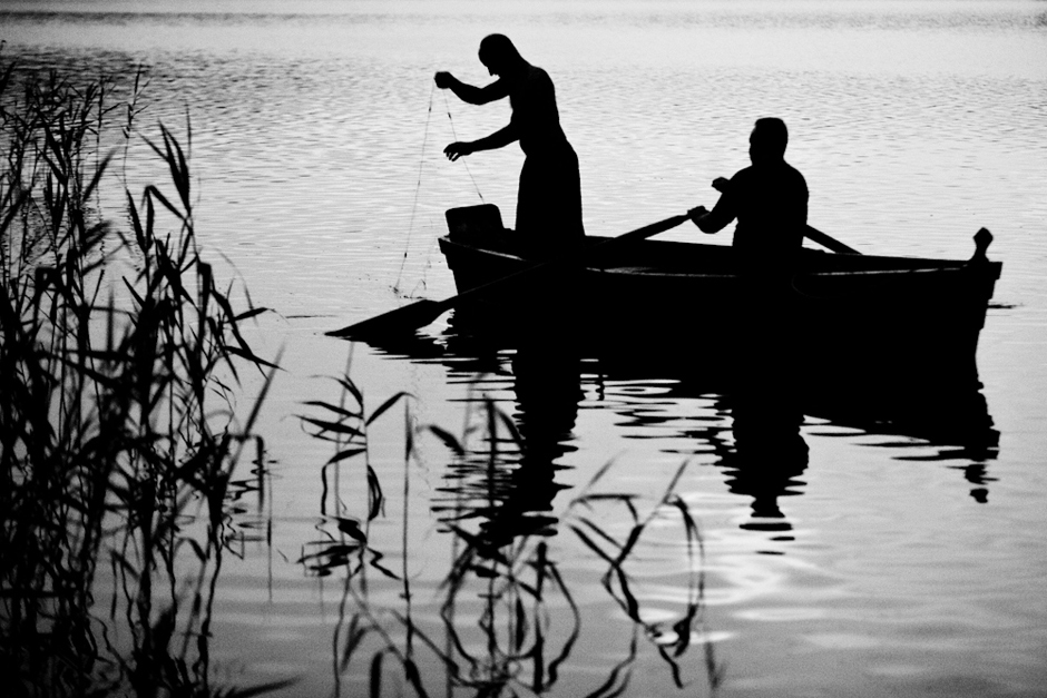 Dirba poroje: vienas irkluoja, o kitas meta tinklus. © Karolis Kavolėlis