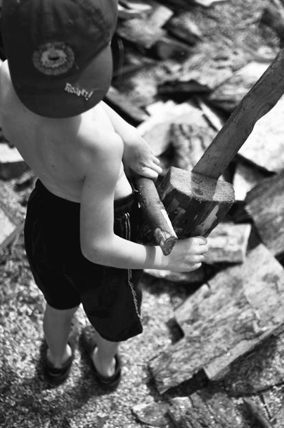 Matas demonstruoja savo rankomis pagamintą medinį pjūklą. Panašu, kad jam tikrai rūpi ūkis ir kas su juo susiję. © Ieva Budzeikaitė