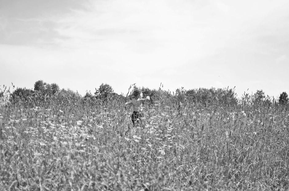Berniukas, išgirdęs atvažiuojantį traktorių, nuskuodė į laukus patikrinti, ar tai tikrai traktorius. © Ieva Budzeikaitė