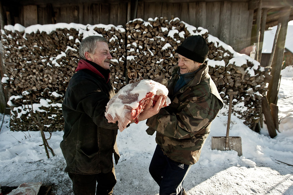 """""""Reznikas"""" (kairėje) perduoda Reginos sūnui (dešinėje) mėsos gabalą. © Vladimiras Ivanovas"""