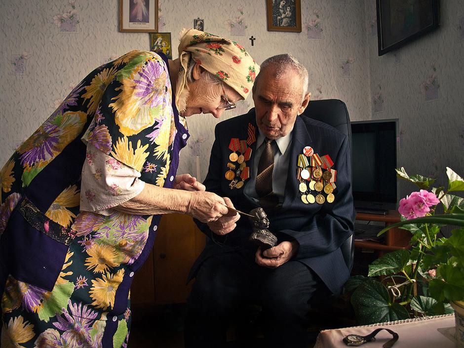 """Deviaten Bronislav. Gimė 1925 m. Gyvena Smorgonyse, Baltarusijoje.   """"Mes buvome stipri karta, nes matėme karą.""""   Aš gyvenau kaimelyje (dabar netoli Voistomo). Prieškaryje tai buvo lenkiška teritorija, o siena su Rusija buvo netoli Molodečno miesto. Kaimelyje kabėjo kvietimas eiti tarnauti į lenkų kariuomenę, bet mus gaudė NKVD. Sykį susitikome su ,,policajais"""" ant takelio. Šokom bėgti: draugas į vieną pusę, aš - į kitą. Įbėgau klojiman ir šieno kupeton nėriau.   Nutariau tarnauti lenkų kariuomenėje. Išvykau į Vilnių. Lietuva tada buvo dar nepriklausoma valstybė. Iš ten mus nuvežė į Bialystoką. Ten mes mokėmės žygiuoti ir šaudyti. Pasitaikydavo dezertyravusių. Juos pagaudavo, teisdavo. Kitą dieną jie ėjo išpažinties pas kunigą, perpiet kasė duobę, o vakare jau joje negyvi gulėjo.  Buvau sužeistas.Tai įvyko 1945m. balandžio 26d. netoli Berlyno. Vokiečių snaiperis pataikė man į žandą. Šovinys išmušė visus dantis. Ligoninėje man subintavo visą galvą. Įstatė vamzdelį, per jį ir gaudavau maistą. Tai tęsėsi kelis mėnesius. Po to dar ilgai negalėjau praverti burnos. Galvoju, kad jei būtų papuolęs sprogstamas šovinys, būčiau likęs išvis be žandikaulio. Dar ir dabar po tiek laiko kalbu sunkiai, nejaučiu liežuvio.   Teko būti ir apsuptyje, ir mediku buvau, nešiojau karabiną su vaistinėle. Sykį besitraukiančių vokiečių mašinoje radau lenkišką 1897m. leidimo maldaknygę ir akinius. Tuos akinius motina naudojo ,o po to ir žmona, - patogūs labai.  P&S. Rankose laiko J. Pilsudskį. © Romualdas Vinča"""