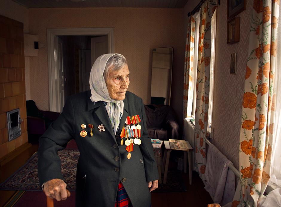 """Ieva Trembač. Gimė 1924 m. Gyvena Smorgonyse, Baltarusijoje.   Ši moteris atvyko gyventi į Smorgonių miestelį iš Oršos kitame Baltarusijos krašte, visai netoli Rusijos. Tai nutiko jai tik baigus mokslus ir negavus siuntimo.   Apie karo metus daug nepasakojo. Vis geru žodžiu paminėdavo savo sūnų ir jo anūkus.  - Kokiame fronte kariavau jau nebepamenu, - pasakojo Ieva. - Pamenu klubą, kur mus palydėti atėjo pusė kaimo ir šokius iki ryto. Pamenu, kaip partizanais buvome. Sprogdindavome, bėgdavome, sprukdavome, o į mus šaudydavo. Kitą dieną viskas iš naujo prasidėdavo.  Paklausiau, kas gi nutiko, kas ir šiandien prisimenate?   - Žinai, buvo viena baisi diena, kai manėme mums galas atėjo. Nutiko taip, jog vokiečių kariuomenė kėlėsi per tiltą. Mums teko slėptis po juo ir kelias valandas laukti, kol jie pereis jį. Po to dar ilgai bijojome kišti nosis lauk.  Muskij Vladimir. Gimė 1924 m. Gyvena Smorgonyse, Baltarusijoje.   """"Kai baigėsi karas, mes maudėmės Baltijos jūroje""""   Iki 1944m. kariavome partizanų būryje, o vasarą, kai miestelis buvo išvaduotas nuo vokiečių, mus paliko čia organizuoti mokyklas ir dirbti mokytojais. Taip aš pradėjau mokytojauti vienoje iš kaimo mokyklų rajone, nes buvau labiausiai išprusęs, t.y. prie lenkų baigęs 7 klases. O vėliau stojau į institutą ir baigiau mokslus.   Tiesa, kokį pusmetį teko kariauti ir reguliariuose daliniuose. Atvežė mus į Šiaulių miestą. Tai buvo 1944 m. liepos vidurys. III Baltarusijos frontas. Vokiečiai buvo rimtai įsitvirtine pajūryje. Jau buvo paskelbta apie Vokietijos kapituliavimą, o mes dar su jais kariavome. Jie juk buvo apsupti ir nieko nežinojo. Kai baigėsi karas, mes maudėmės Baltijos jūroje ties Palanga. © Romualdas Vinča"""