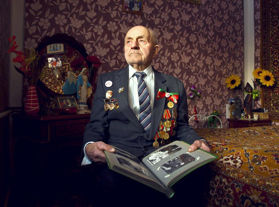 """Kuzma Ivan. Gimė 1925 m. Gyvena Smorgonyse, Baltarusije.  Kai 1939 m. prasidėjo karas aš mokiausi lenkiškoje mokyklėlėje, septintoje klasėje. Taip ir likau jos nebaigęs. Tarnavau lenkų kariuomenėje, vėliau buvau sužeistas. Subintuota galva ir ranka nutariau grįžti į Salų kaimą, pas tėvus. Čia mane sulaikė NKVD. Atėmė lenkiškus dokumentus ir pasakė, jog jei mes taip liuosuotume savo kareivius, greitai liktume be kariuomenės. Buvau išsiųstas į Minską.    Buvo žiema. Iš čia į Rusiją, - atstatinėti sugriauto Briansko miesto. Vadinomės mes """"užnugario dalinys"""". Statėme įvairios paskirties pastatus, tiltus. Turėjome ir ginklus, nes miškuose slapstėsi """"Juodosios katės"""" ar """"Banderos"""" gaujos.  Kai atvežė mus į Brianską, miestas buvo vien griuvėsiai, o žmonės gyveno pusrūsiuose. Išdavė mums kastuvus ir laužtuvus ir turėjome kasti įšalusią žemę ir pasistatyti sau žiemines. Vietoj durų kabėjo skuduras. Patalpą, kur gyveno 40-50 kareivių, šildė pečiukas (,,buržuika""""), o šviesa sklido iš mažo langelio sienoje. Miegojome ant eglės šakų, tiesiog savo darbiniuose rūbuose. Gultis turėjai ant dviejų žmonių ir taip po truputi įsisprausdavai tarp jų ant gulto. Trūko vietų. Greitai mus ėmė pulti blusos ir kitokie parazitai. Pirtis buvo dvi vandens bačkos, kurias mes turėjome šildyti įkaitinta geležim, paimta iš laužo. Kai nusiprausdavai, rengtis tave išspirdavo į lauką. Nesvarbu, jog kieme žiema.    1945m. gegužės 9 d. dirbome prie geležinkelio. Šalia sustojo traukinys ir iš vagonų pasipylė kareiviai. Jie linksminosi, šūkavo ir grojo armonika. Pamatę mus jie apmirė.   - Kas jūs tokie? Pasiteiravo mūsų.  - Mes - užnugario dalinys, - toks buvo mūsų atsakymas.  Jie buvo švarūs, o mes - purvini ir pavargę. Nors ta diena buvo džiugi, džiaugtis ja neturėjome jėgų.   1950 m. grįžau į tėvynę. Dirbau statyboje, pastačiau miestelyje pirmą mokyklą, kuri lig šiol stovi ir sėkmingai veikia. Pasistačiau namą, sutikau būsimą žmoną, ir jau 61m. kaip mes nugyvenome kartu. Gaila tik, kad prieš porą metų st"""