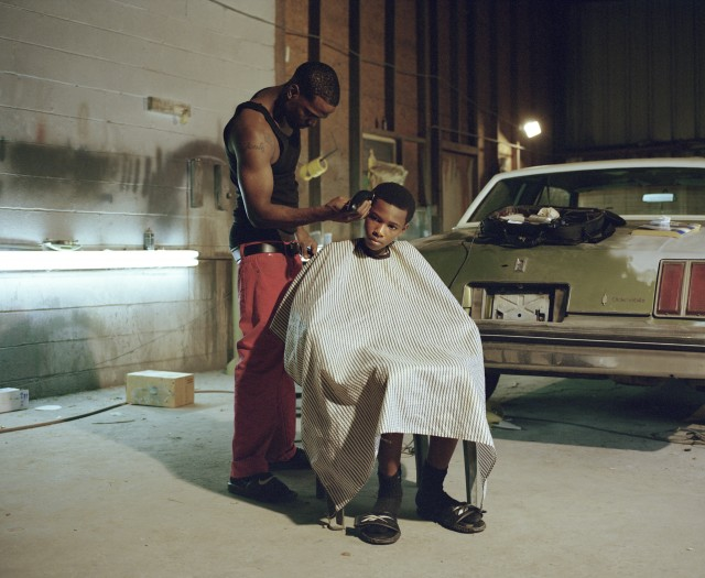 Blessing Montana is giving a haircut to his brother Satino Montana in the garage where they work. Baton Rouge, LA