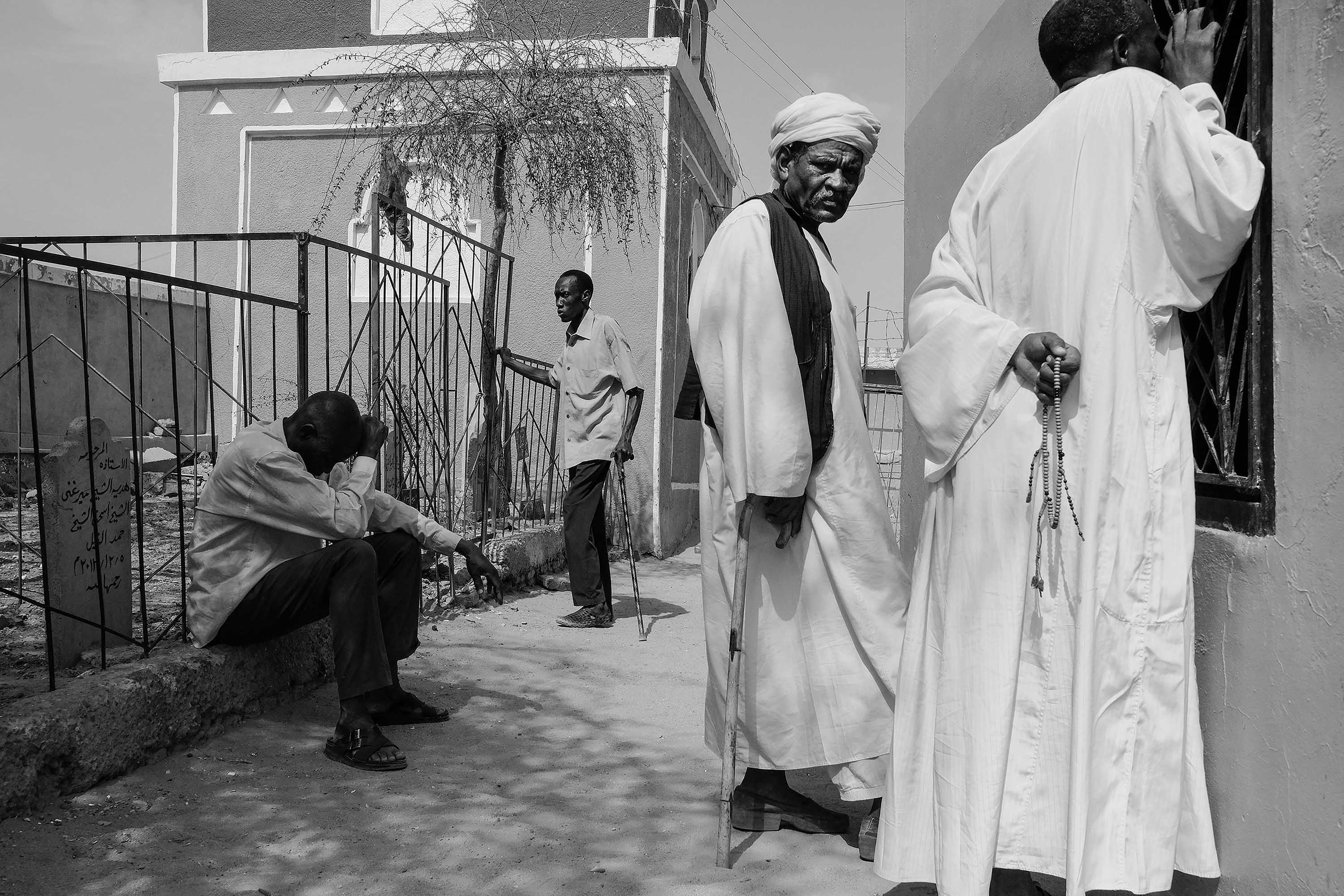 01. Sufis gathered around Hamed El Nil mausoleaum listen to the songs echoing from within. Omdurman. Sudan. 2017